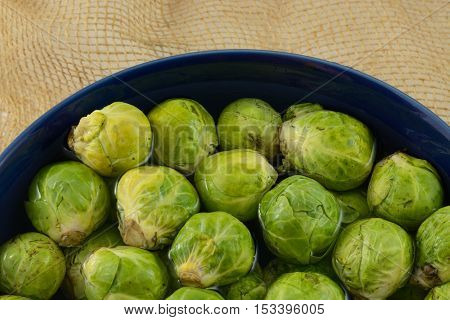 Brussel Sprouts soaking in bowl of water to loosen agricultural dirt