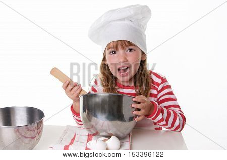 Cute Little Girl With a Chef Hat and Apron Baking.  She is mixing ingredients with a wooden spoon and looking at the camera having fun.