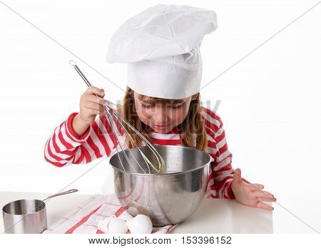 Cute Little Girl With a Chef Hat and Apron Baking.  She is whisking eggs and looking into the bowl having fun