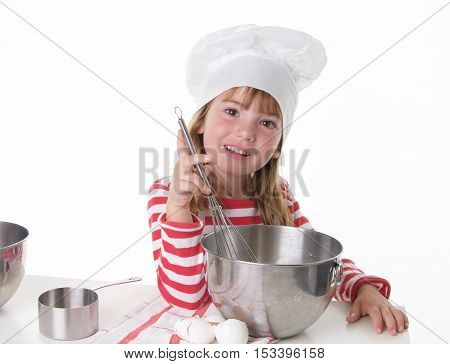 Cute Little Girl With a Chef Hat and Apron Baking.  She is smiling at the camera with a whisk in her hand