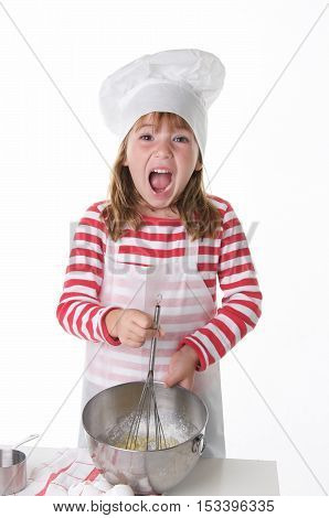 Cute Little Girl With a Chef Hat and Apron Baking.  She is using a whisk to mix ingredients and is very excited