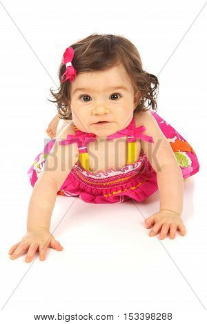 Cute baby girl on a white background wearing a pretty dress crawling