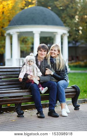 happy parents with daughter sitting on bench against backdrop of mirador in park