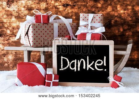 Chalkboard With German Text Danke Means Thank You. Sled With Christmas And Winter Decoration. Gifts And Presents On Snow With Wooden Background And Bokeh Effect.