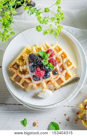 Tasty berries with waffels for breakfast on white table
