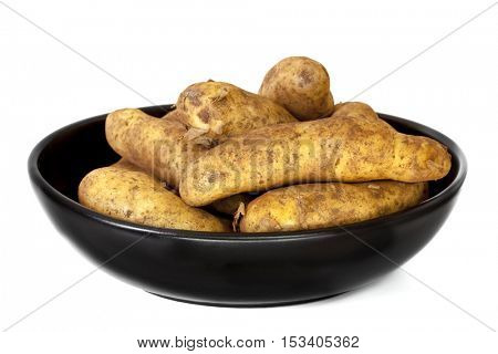 Raw unwashed fingerling potatoes in black dish.  Isolated on white.