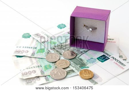 Ring in gift wrapping standing on thousandths of bills and coins
