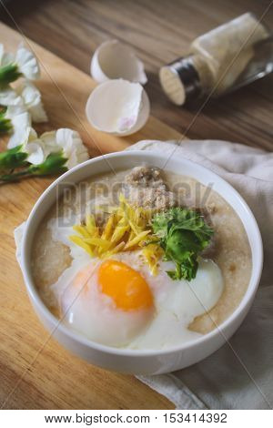 rice porridge with ground pock vintage tone with white flowers on wood background Thai Food Thai Cuisine Beast Breakfast