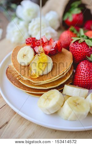 pour syrup on stack of pancake with strawberry and slice of banana on whie place with wooden background
