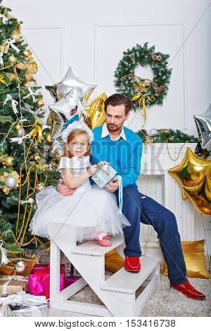 Father and daughter with gifts near a Christmas tree. Father hugging daughter and little cute girl unties the bow on the gift. The festive mood. Family celebration.