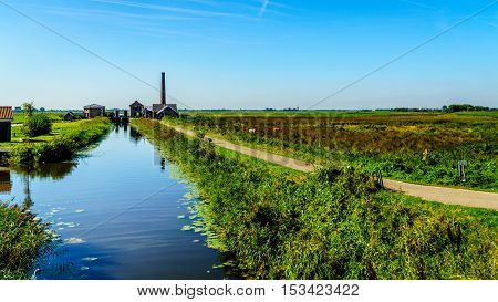 The historic Nijkerk Pumping Station or Nijkerk's Gemaal at Veluwemeer under blue sky near the town of Nijkerk in the Netherlands