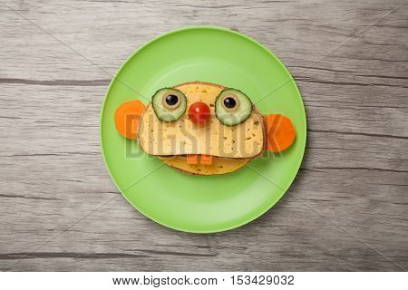 Sloth made of bread and cheese on plate and board