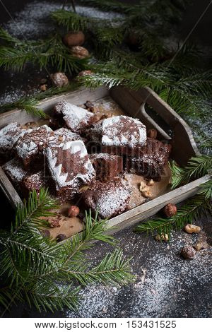 Christmas card. Christmas tree on a black wooden background with sweets and biscuits. The original idea of Christmas. Chocolate cake. Brownie With tree of powdered sugar. New Year