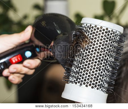 Detail of drying hair with hair dryer and brush at the hairdresser.