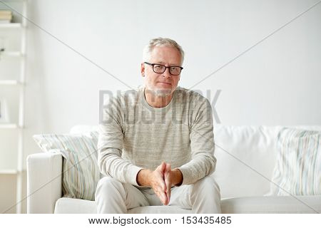 old age, comfort and people concept - smiling senior man in glasses sitting on sofa at home