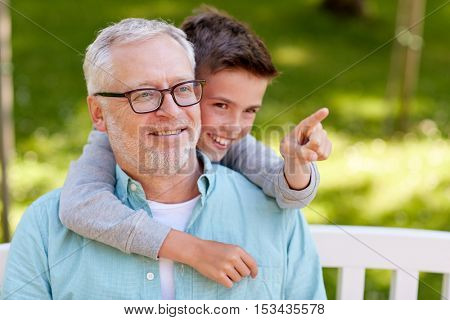 family, generation, relations and people concept - happy grandfather and grandson pointing finger to something at summer park