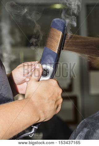 Close-up of a hairdresser making curles with brown hair.