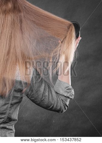 Everyday hygiene and care about good look. Back view of blonde casual girl combing her long straight hair. Woman using black comb hairbrush.