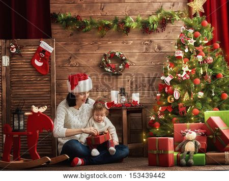 Merry Christmas and Happy Holidays! Cheerful mom and her cute daughter baby girl exchanging gifts. Parent and little child having fun near Christmas tree indoors. Loving family with presents in room.