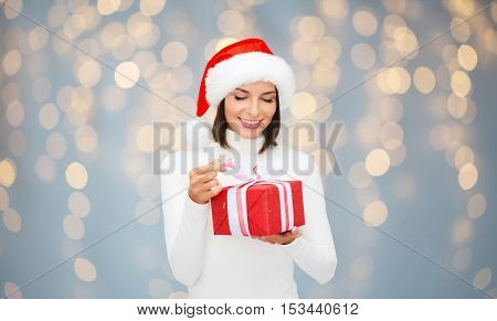 christmas, people and holidays concept - smiling woman in santa helper hat with gift box over lights background