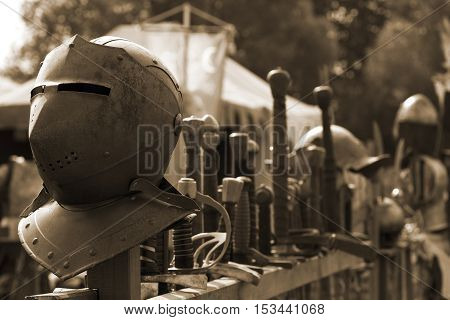 Old medival weapons and some helmets, stacked in a row.