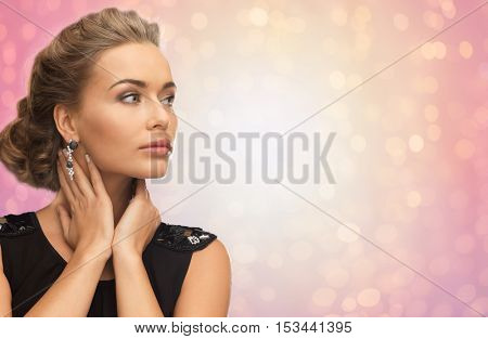 beauty, jewelry, holidays and people concept - beautiful woman in evening dress wearing diamond earrings over rose quartz and serenity lights background