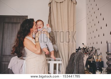 happy mother and baby son playing together at home mom holding and kissing her 11 month old boy cozy lifestyle
