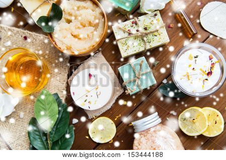 beauty, spa, therapy, bodycare and wellness concept - natural body care cosmetics on wood over snow