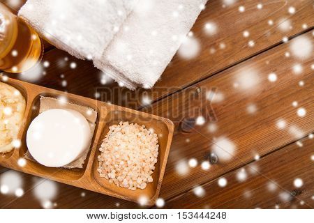 beauty, spa, bodycare, natural cosmetics and wellness concept - soap with himalayan pink salt and bath towels on wooden table over snow