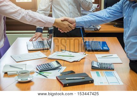 Business Concept Of Office Working, Young Business Men Shaking Hands With Business Background.