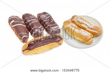 Several eclairs with different chocolate icing and two eclairs with sugar sprinkling on saucer on a light background