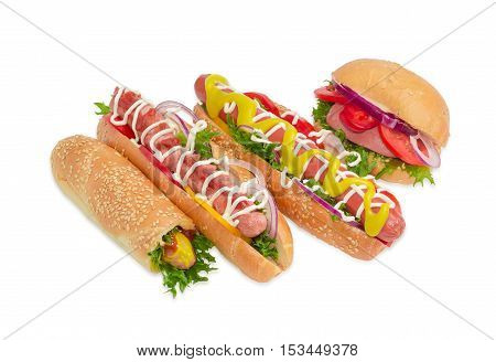 Several different hot dog with frankfurter mustard mayonnaise ketchup and vegetables in buns with sesame seeds on a light background