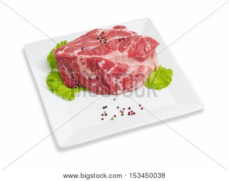 Piece of a fresh uncooked pork neck black and red pepper lettuce on a white square dish on a light background