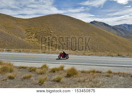 Otago New Zealand - February 2016: Motorbike riding pass scenic lookout of Lindis Pass on State Highway 8 (Tarras - Omarama - Lindis Pass Road) lies between the valleys of the Lindis and Ahuriri Rivers south island of New Zealand.