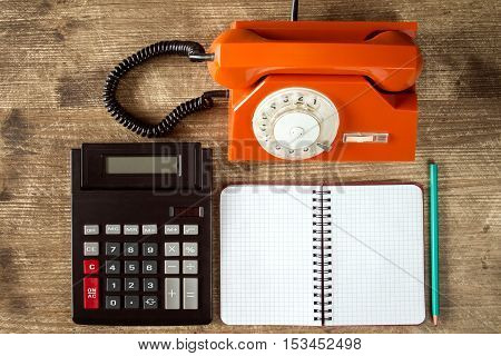Rotary telephone calculator and blank notebook on wooden table. Top view.