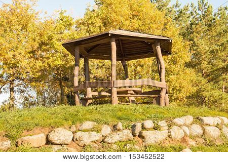 Wooden arbour among the trees in on the hill