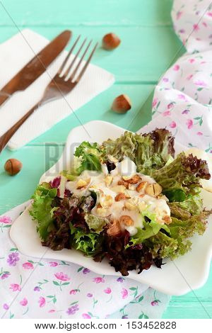 Mix of salad leaves with sauce and chopped hazelnuts on a plate. Radicchio, lettuce, iceberg, frieze mix. Vegetarian food. Fork, knife, napkin, raw hazelnuts on a wooden background. Closeup
