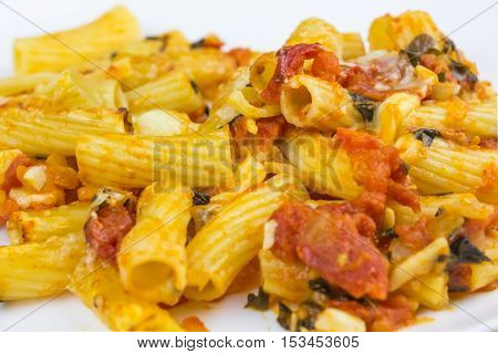 Baked tortiglioni pasta with tomato sauce mozarella and parmesan cheese in plate