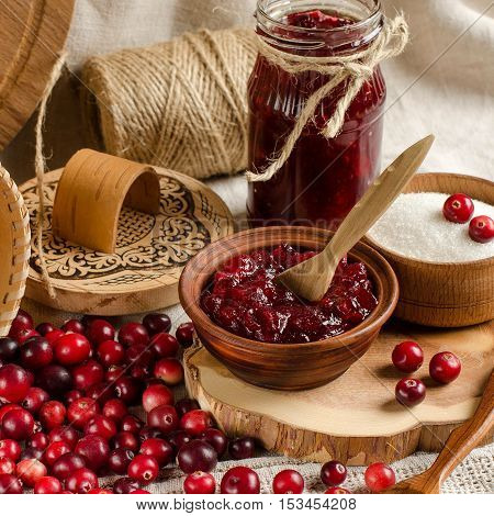 The red berries. Cranberry. Jam from cranberries. Birch bark basket. Sugar in a bowl. Wood planks. Glass jar of jam. A bright background. A rustic style. Cooking.