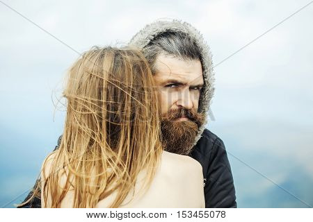 Handsome man hipster with beard and moustache in warm coat and hood hugs undressed girl outdoors on nature