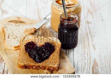 Homemade Peanut Butter And Jelly Sandwich On Wooden Background