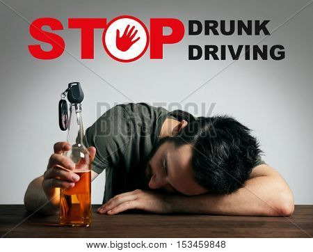 Drunk young man with car key and beer bottle at bar. Text STOP DRUNK DRIVING on background.