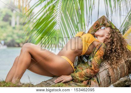 Beautiful woman in bikini lying on palm on tropical sea beach