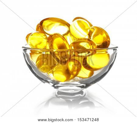 Cod liver oil capsules in glass bowl isolated on white