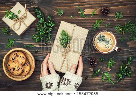 Opening Christmas present. Woman's hands holding decorated gift box on rustic wooden table. Ideal Christmas morning. Overhead flat lay top view