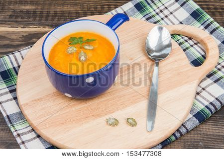 Pumpkin Soup Served On A Wooden Cutting Board