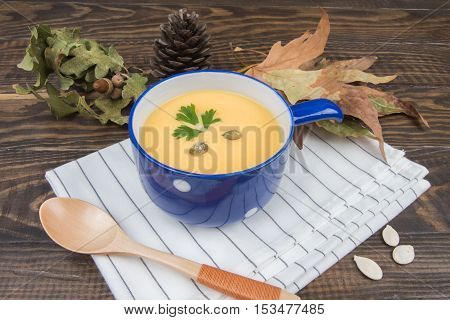 Pumpkin Soup, Spoon And White Napkin On A Dark Wooden Background