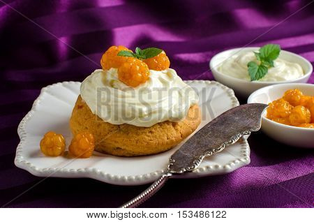 Cream cake on a white saucer. A vintage knife. Cloudberries and cream in bowls. Purple background.