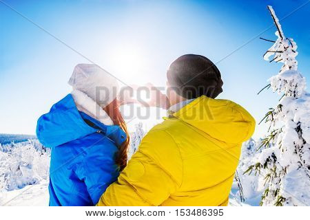 wintersports couple catching the sun making heart sign