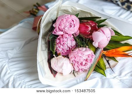 Bouquet of pink peonies in kraft paper on bed - gift for girl